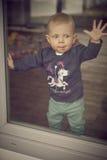 Младенец смотря вне окно Стоковые Изображения RF
