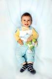 Ребёнок на голубой усмехаться Стоковые Изображения