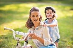 Ребёнок обнимая мать около велосипеда в парке Стоковое Фото