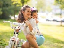 Ребёнок обнимая мать около велосипеда в парке Стоковые Изображения RF