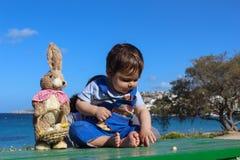 Ребёнок окруженный с концепцией пасхи цветков стоковая фотография rf