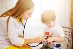 Ребёнок педиатра рассматривая Доктор используя стетоскоп для того чтобы слушать к ребенк и проверяющ сердцебиение стоковая фотография rf