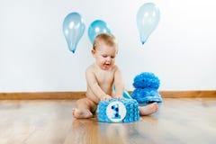 Ребёнок празднуя ее первый день рождения с изысканными тортом и ба Стоковые Изображения RF