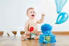 Ребёнок празднуя ее первый день рождения с изысканными тортом и ба Стоковое фото RF