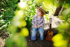 Ребёнок при красное вьющиеся волосы сидя с гитарой в парке стоковое фото rf