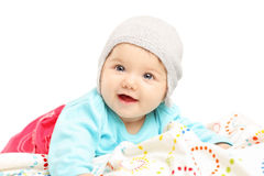 Ребёнок при шляпа лежа вниз и усмехаясь Стоковая Фотография