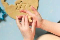 Ребёнок ребенка отжимая резец печенья звезды в тесто печенья сахара над голубым тонизированным взглядом инструментов Сердце и зве Стоковое Изображение