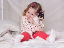 Ребёнок сидит на кровати и обнимает собаку Стоковое фото RF