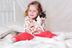 Ребёнок сидит на кровати дома с собакой Стоковое фото RF