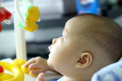 Ребёнок сидит на ходоке младенца и смотреть вверх для вахты что-то Стоковые Изображения