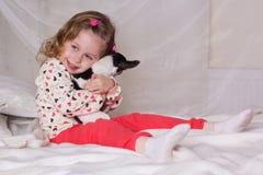 Ребёнок сидя на кровати и держа собаку Стоковые Фото
