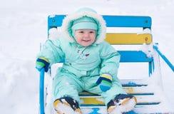 Ребёнок сидя на стенде в парке в зиме Стоковые Фото