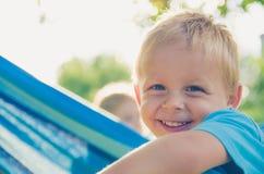 Ребёнок смеется над на солнечный день Другой ребенок на гамаке позади сада Стоковое Изображение