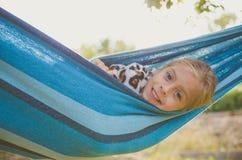 Ребёнок смеется над на солнечный день Она лежит в голубом гамаке Стоковые Фотографии RF
