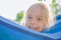 Ребёнок смеется над на солнечный день Она лежит в голубом гамаке Стоковая Фотография