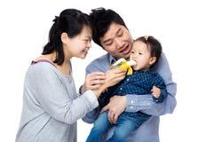 Ребёнок счастливой семьи подавая с бананом стоковая фотография