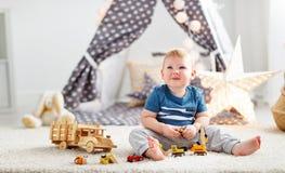 Ребёнок с автомобилями игрушки в игровой ` s детей Стоковое Изображение RF