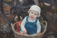 Ребёнок с глазами океана темносиними и рубашка pinky щеки нося белые и джинсы одевают и шляпа handmade ремесла крошечная сидя в b Стоковое Изображение