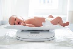 Ребёнок утяжеления на масштабе Стоковые Фотографии RF
