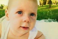 Ребёнок outdoors в зеленом лесе вползая на траве на белом одеяле Стоковая Фотография