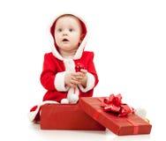 Ребёнок Santa Claus с коробкой подарка на белизне Стоковые Фото
