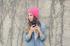 Ревнивая женщина проверяя ее мобильный телефон ` s парня Sms чтения женщины секретные на ее мобильном телефоне Она одета в всколь Стоковое Фото
