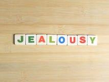 Ревность слова на деревянной предпосылке стоковые изображения rf