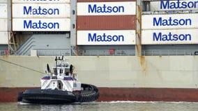 РЕВОЛЮЦИЯ буксира нажимая грузовой корабль МАУИ к доку Стоковое фото RF
