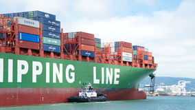 РЕВОЛЮЦИЯ буксира помогая ЗИМЕ грузового корабля CSCL для того чтобы провести маневр Стоковые Изображения RF