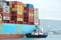 РЕВОЛЮЦИЯ буксира помогая маневру GERD MAERSK грузового корабля Стоковая Фотография