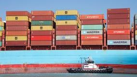 РЕВОЛЮЦИЯ буксира AmNav помогая GUTHORM MAERSK для того чтобы провести маневр в порт Окленд Стоковые Изображения