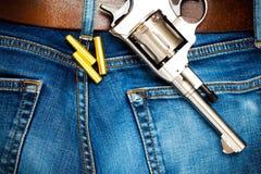 Револьвер с патронами на старых голубых джинсах Стоковые Фото