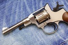 Револьвер Nagan на старых голубых джинсах Стоковое Изображение RF