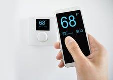 Регулировать температуру с smartphone стоковые изображения rf