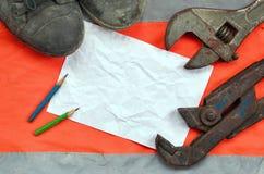 Регулируемые ключи с старыми ботинками и лист бумаги с 2 карандашами Натюрморт связал с ремонтом, железной дорогой или трубопрово стоковые фотографии rf