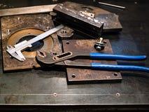регулируемые плоскогубцы и крумциркули на верстаке металла стоковое изображение rf