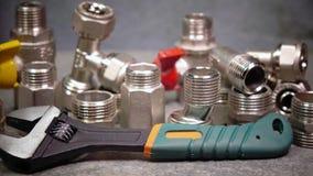 Регулируемый гаечный ключ metalwork на фоне выключения воды и соединяясь запорные клапаны для водоснабжения сток-видео