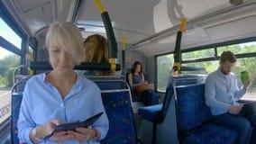 Регулярные пассажиры пригородных поездов используя прибор мультимедиа на автобусе 4k видеоматериал