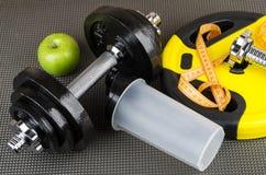 Регулируемые гантели, вес, пластичный шейкер, яблоко и измерения Стоковая Фотография