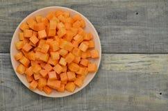 Режет кубы моркови в белой плите на деревянной предпосылке Стоковое фото RF
