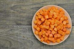 Режет кубы моркови в белой плите на деревянной предпосылке Стоковая Фотография RF