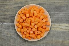 Режет кубы моркови в белой плите на деревянной предпосылке Стоковая Фотография