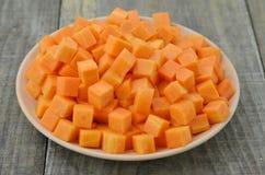 Режет кубы моркови в белой плите на деревянном столе Стоковое фото RF