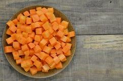 Режет кубы моркови в черной плите на деревянной предпосылке Стоковая Фотография RF
