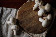 Режут грибы на доске кухни Стоковые Изображения