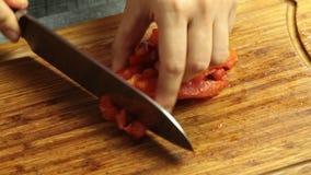 Режущ испеченный болгарский перец и варить спагетти Bolognese в кухне сток-видео