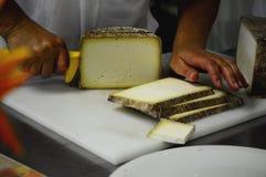 Режущ традиционное вызревание в деревянном случае - крупный план сыра долины Taleggio ремесленника на отрезать на разделочной дос стоковые фото