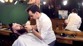 Резать вискеров, брея Сконцентрированный молодой парикмахер в действии Рабочее место, отражение в зеркале на предпосылке r сток-видео