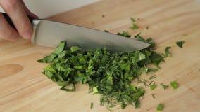 Резать зеленые цвета на доске с ножом акции видеоматериалы