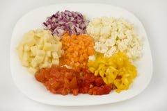 Резать различные овощи в кубики стоковые фото